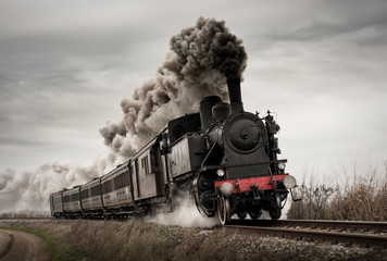 Photo sur Aluminium Voies ferrées Vintage steam train with ancient locomotive and old carriages runs on the tracks in the countryside