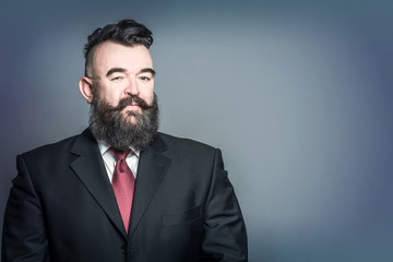 Adult bearded man in a suit with mohawk hairstyle on a blue background