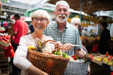 Mature couple shopping vegetables and fruits on the market. Healthy diet. Wall mural