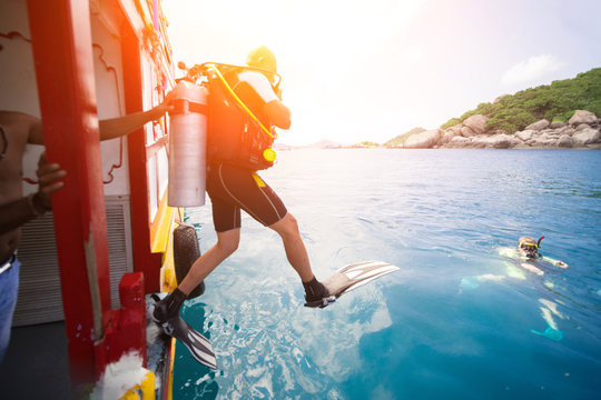 Male diver jumps into the sea from a yacht.