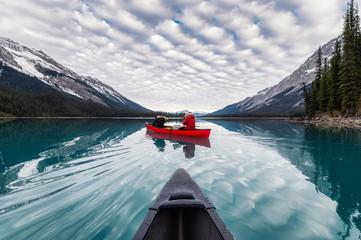 Traveler canoeing on Maligne lake with canadian rockies reflection in Spirit Island at Jasper national park