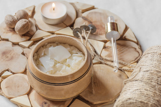 Tools for making candles of white soy wax flakes, essential oil, wicks on wooden background. Front view. Ecological lifestyle