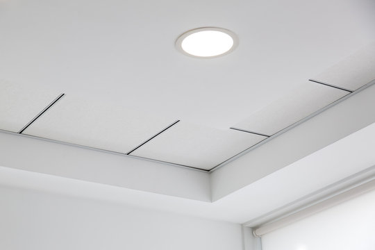 multi-level ceiling with three-dimensional protrusions and a suspended tiled ceiling with a built-in round led light.