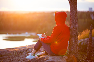 Man in hoodie writing in notebook, sitting on top of the rock. scenic view of landscape. beautiful sunset. Finland