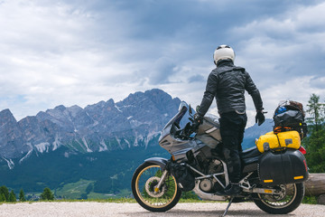 Back view of stylish biker on adventure touring motorcycle in full equipment on dirt road, Look at distance on top of Dolomites mountains, travel concept, copy space. Cortina Ampezzo, Italy Fototapete