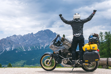 Concept of destination. conquering the top, two hands up, biker man with touring motorcycle on dirt road,