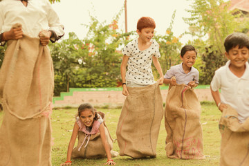 Children's playing potato sack jumping race at park outdoor - kids falling and having fun while playing gunny sack race.