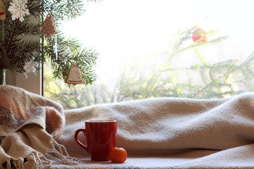 red mug, plaid green Christmas tree with decorations in front of the window on a festive day. cozy home coffee break