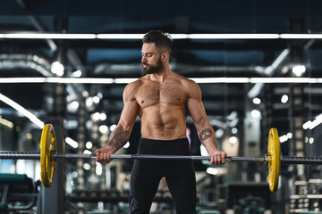 Wall Mural - Young muscular guy training with barbell at gym