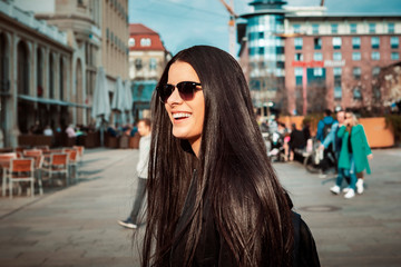 young Latina with long hair and sunglasses walking on a busy street.