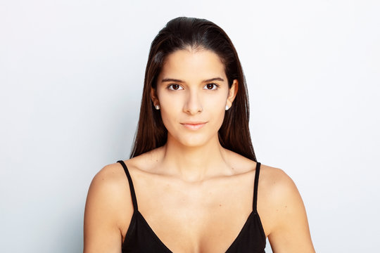 studio portrait of a young Latina with long hair, wearing a black tank top, with white background