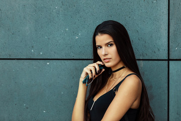 young Latina with long hair, wearing a tank top, jewelry and necklace in front of a cement background