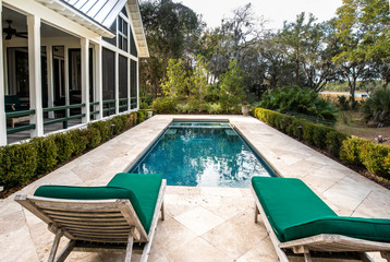 Beautiful back yard pool behind luxury home with garden