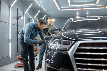 Two car service workers examining vehicle body for scratches and damages while taking a car for professional automotive detailing