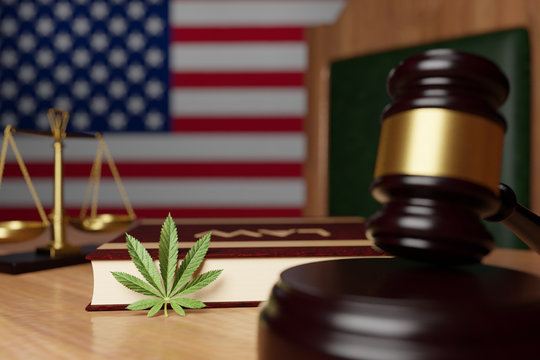 Legalization of cannabis in the United States, the hammer of the judge, the scales of justice, the book with the inscription Law and cannabis leaf lie on the desktop of the judge on the background