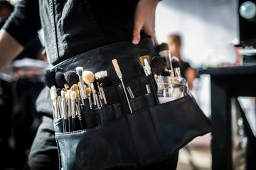 Wall Mural - Close-up on a make-up artist's belt during the fashion show, backstage photo.