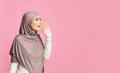Muslim girl in hijab shouting at copy space, making announcement