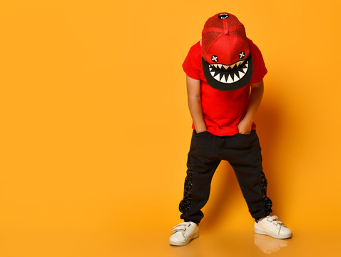 Young guy boy in a red T-shirt and dark pants, white sneakers and a funny cap posing on a free copy space on a yellow background