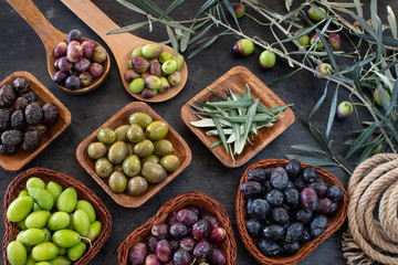 Mixed types of olive in the bowls and olive oil on the table