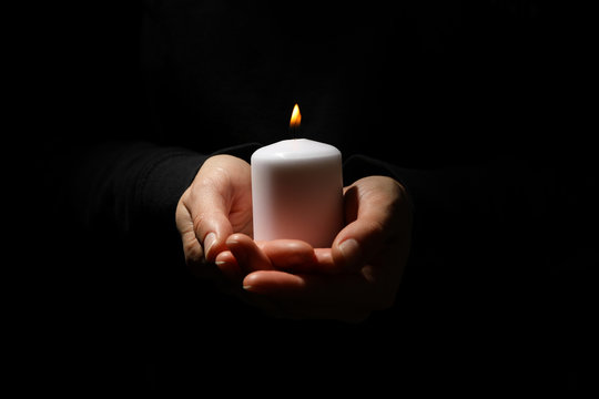Woman holds candle on black background, front view Woman holds candle on black background, front view