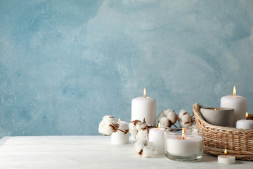 Poster de jardin Detente Burning candles, basket and cotton on white wooden table, space for text