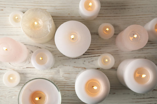 Different burning candles on wooden background, top view