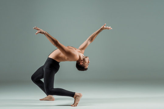 side view of handsome dancer with closed eyes in black leggings dancing contemporary on dark background