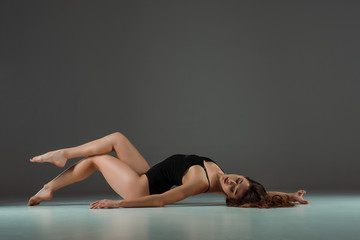 attractive dancer in black bodysuit dancing contemporary on dark background