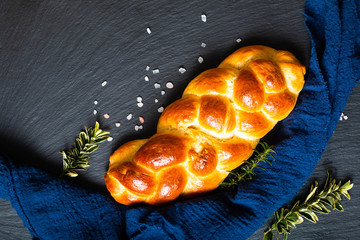 Foto auf Acrylglas Brot Homemade food concept fresh baked bread braid challah or brioche on black slate stone with copy space