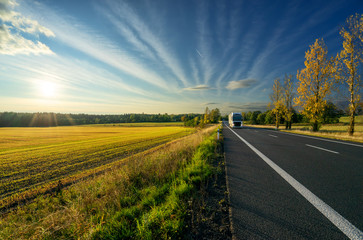 Fotobehang - White truck arriving from a distance on an asphalt road in autumn rural landscape at sunset