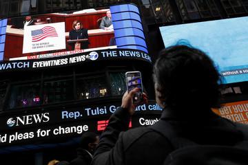A man takes photo of House Speaker Nancy Pelosi (D-CA) on a jumbotron outside ABC News studios n New York