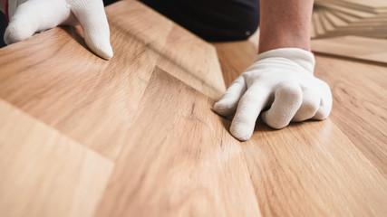Installing laminated floor, detail on man hands in white gloves fitting wooden tiles