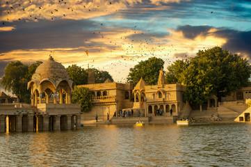 Sandstone chattri domes with steps on gadi sagar lake in jaisalmer at dusk