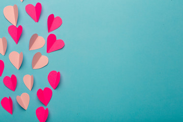 Love (Valentine's day) background or wedding background. Pink and red paper hearts on a blue pastel background. Love concept
