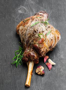Whole roast lamb leg on black stone background