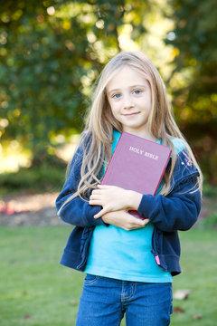 Little Girl Holding Bible Outdoors