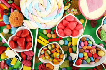 candies with jelly and sugar. colorful array of different childs sweets and treats on green background