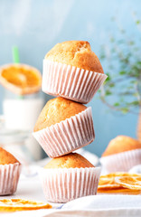 Stack of orange muffins in white paper muffin cups close-up, blue background. Homemade sweet pastries, delicious sweet breakfast.