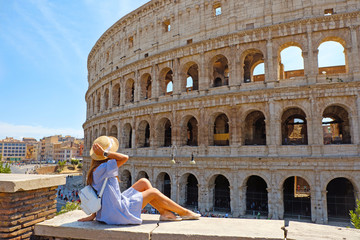 Papiers peints Rome Travel woman in romantic dress and hat sitting and looking on Coliseum, Rome, Italy. Beautiful tourist girl with backpack near Colosseum. Young woman enjoy summer Italian vacation in Europe.