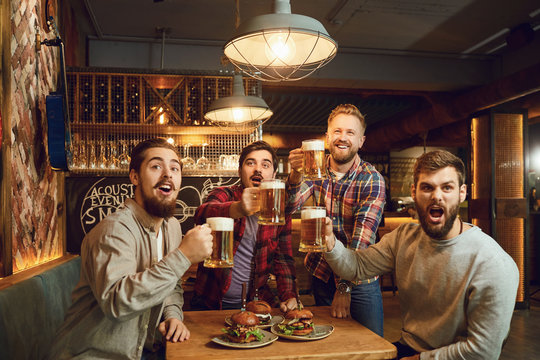 A group of guys watching sports on tv in a pub bar.