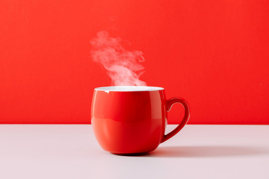 Steaming coffee cup on red background. Red сoffee cup with steam. Front view, copy space