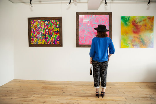 Japanese woman wearing hat standing in front of abstract painting in an art gallery.