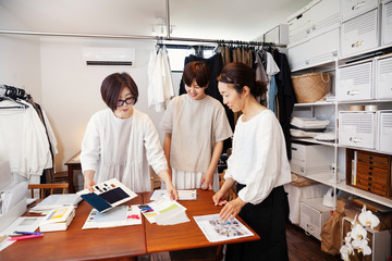 Three Japanese women standing at a table in a small fashion boutique, looking at fabric samples. Wall mural
