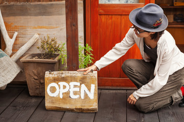 Japanese woman wearing hat and glasses kneeling in front of a leather shop, holding Open sign.