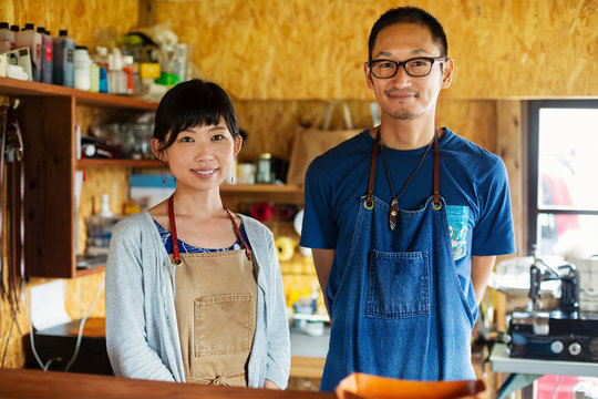 Japanese woman and man wearing blue apron standing in a leather shop, smiling at camera.