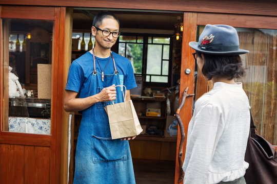 Japanese woman and man wearing blue apron and glasses standing outside a leather shop, holding shopping bag.