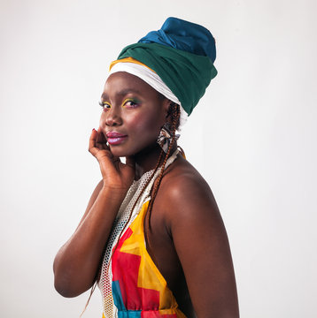 Studio fashion portrait of young African woman in summer dress and ethnic head wrap, white background.