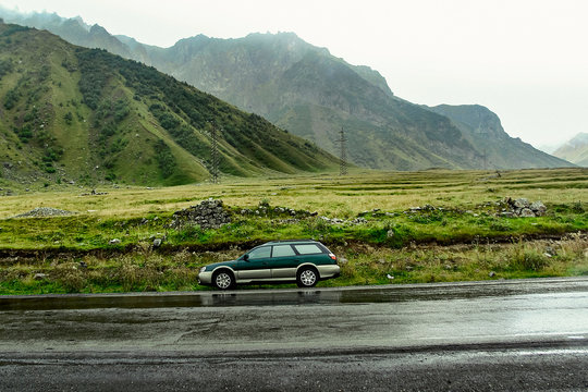 Green wagon Subaru Outback BH stopped on a mountain road