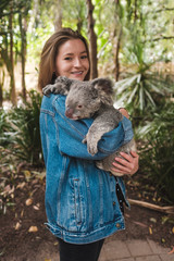 Wall Murals Koala Magnetic island, Australia: Young happy woman holding koala and smiling