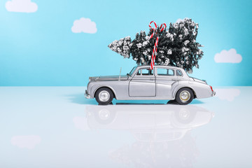 Tiny toy Christmas tree tied onto a vintage toy car
